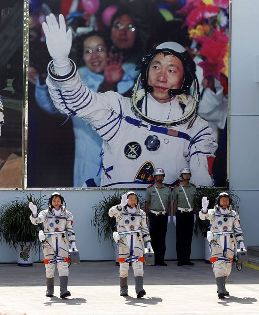 China's astronauts from left., Liu Yang, Jing Haipeng and Liu Wang wave and walk before a giant portrait of China's first astronaut Yang Liwei, as they depart for the Shenzhou 9 spacecraft rocket launch pad at the Jiuquan Satellite Launch Center in Jiuquan, China, Saturday, June 16, 2012