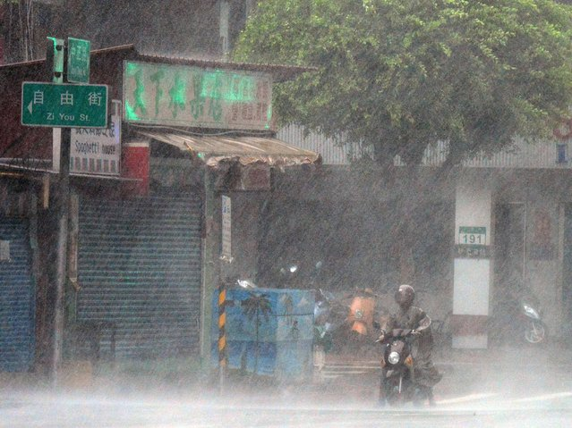 A motorcyclist stops in the rain brought by Typhoon Matmo in Xindien district in New Taipei City on July 23, 2014. Typhoon Matmo pounded Taiwan with fierce winds and downpours, leaving five people injured, shuttering financial markets, and interrupting rail and air transportation. (Photo by Sam Yeh/AFP Photo)