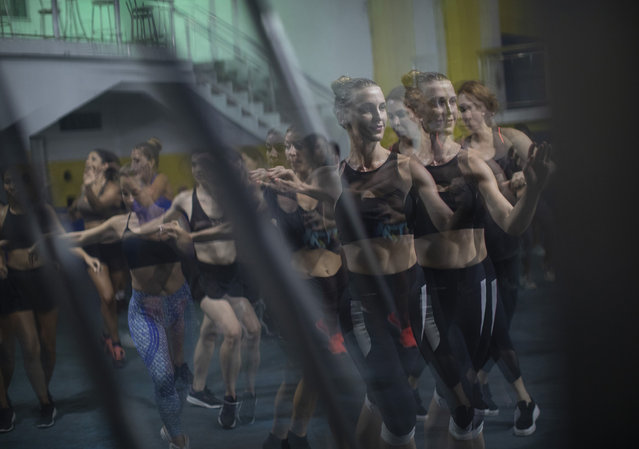 In this January 15, 2020 photo, performers train at the Paraiso de Tuiuti samba school in Rio de Janeiro, Brazil. During classes, casually dressed students can be seen brushing their feet in a quick succession of steps, their hips swinging to the right and left while keeping their heads and shoulders as still as possible. (Photo by Silvia Izquierdo/AP Photo)
