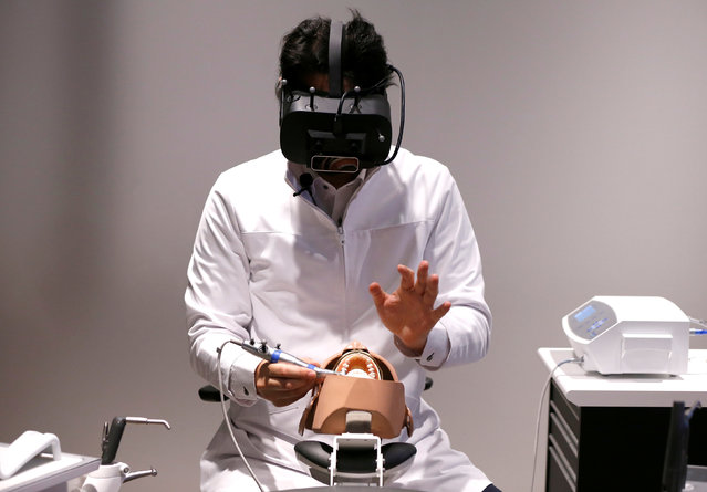 A dentist wearing a VR headset, displaying X-ray photographs and other detailed information of a patient three dimensionally, demonstrates VR simulation program for dental surgeons (called WK2 Project), jointly developed by J. Morita Corp. and Realize Mobile Communications Corp., in Tokyo, Japan April 21, 2017. (Photo by Issei Kato/Reuters)