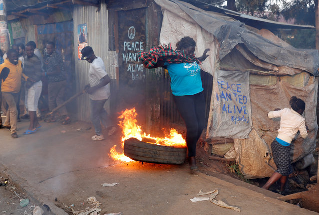A woman jumps as supporter of opposition leader Raila Odinga set up flaming tyre barricade in Kibera slum in Nairobi, Kenya, August 9, 2017. (Photo by Goran Tomasevic/Reuters)