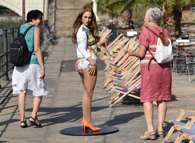 A wax figure depicting Jennifer Lopez by wax museum Madame Tussauds dressed in a new set of clothes attracts the attention of pedestrians during a press event at a beach bar in Berlin,†Germany, August 21, 2015. (Photo by Jens Kalaene/EPA)