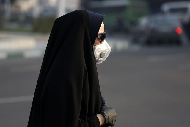 """A pedestrian wearing a face mask crosses  a square in western Tehran, Iran, Saturday, February 29, 2020. Iran is preparing for the possibility of """"tens of thousands"""" of people getting tested for the new coronavirus as the number of confirmed cases spiked again Saturday, Health Ministry spokesman Kianoush Jahanpour said, underscoring the fear both at home and abroad over the outbreak in the Islamic Republic. (Photo by Vahid Salemi/AP Photo)"""