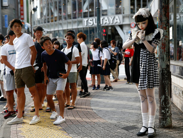 """Pedestrians look at """"doll"""" model Lulu Hashimoto standing on the street during a photo opportunity for Reuters in Tokyo, Japan August 23, 2017. (Photo by Kim Kyung-Hoon/Reuters)"""