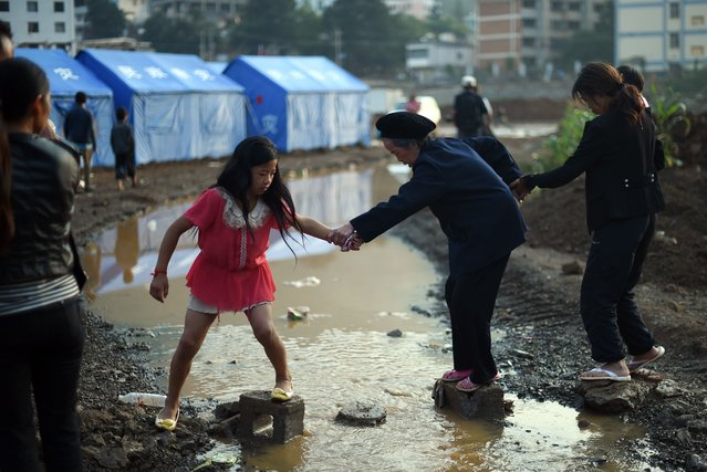 A young girl helps an elderly woman (C) cross a small creek near tents set up for earthquake survivors at Longtoushan, in China's southwest Yunnan province on August 6, 2014. At least 589 people have died in the 6.1 magnitude earthquake that hit on August 3, officials said on August 6, marking a sharp increase in the death toll. (Photo by Greg Baker/AFP Photo)
