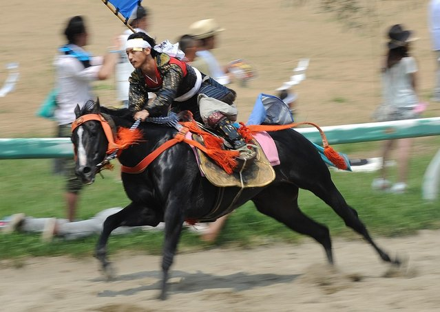 """A local man in samurai armor race horses during the annual Soma Nomaoi Festival in Minamisoma, Fukushima Prefecture, on July 29, 2012. Some 400 horses and thousands of people took part in the 1,000-year-old """"Soma Nomaoi"""", or wild horse chase, at the weekend in the shadow of Japan's crippled Fukushima nuclear plant. (Photo by Toru Yamanaka/AFP Photo)"""