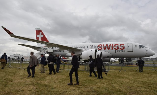 Plane enthusiasts look at a Swiss C-Series plane on display at The Farnborough International Airshow in Farnborough, Britain, 12 July 2016. (Photo by Hannah Mckay/EPA)