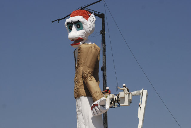 Workers prepare the towering Zozobra marionette for its annual burning at a city park in Santa Fe, N.M., on Friday, September 1, 2017. High anxiety about White House politics, hurricane flooding and even the threat of nuclear war with North Korea is adding an extra spark to the annual destruction of the effigy to gloom and doom. Inside the six-story puppet are reams of crumpled, handwritten notes about recent troubles and travails that people hope to leave behind. (Photo by Morgan Lee/AP Photo)