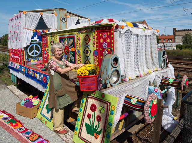 "German peace activist and co-initiator Christa Senberg stands in front of an old diesel locomotive covered by a colourful knitted garment in Zossen, Germany, 26 August 2015 (issued 27 August). The movement ""Knitting for Peace"" is held for the second time after a huge success in 2013, where many dedicated knitting and crochet fans from all over Germany and neighbouring countries turned the diesel locomotives into symbols for piece. (Photo by Patrick Pleul/EPA)"