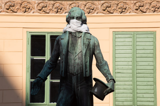 The statue of Johann Nestroy adorned with a protective mask on March 23 in Vienna, Austria. The coronavirus and the disease it causes, covid-19, are having a fundamental impact on society, government and the economy in Austria. Public life has been restricted to the essentials in an effort by authorities to slow the spread of infections. Hospitals are scrambling to increase their testing and care capacity. An economic recession seems likely as economic activity is slowed and many businesses are temporarily closed. Schools, daycare centers and universities remain shuttered. And government, both federal and state, seek to mobilize resources and find adequate policies to confront the virus and mitigate its impact. (Photo by Thomas Kronsteiner/Getty Images)