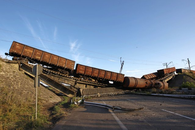 Train wagons are seen on the destroyed railway bridge which collapsed during the fighting between the Ukrainian army and pro-Russian separatists, over a main road leading to the eastern Ukrainian city of Donetsk, near the village of Novobakhmutivka, north of Donetsk city, August 19, 2014. (Photo by Valentyn Ogirenko/Reuters)