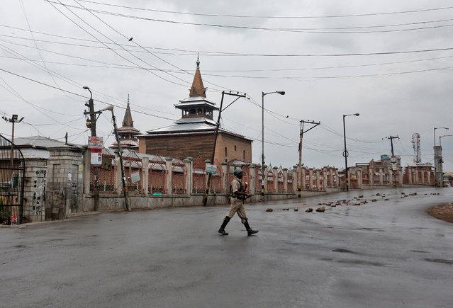 An Indian policeman crosses a deserted road during a curfew in Srinagar July 18, 2016. (Photo by Danish Ismail/Reuters)