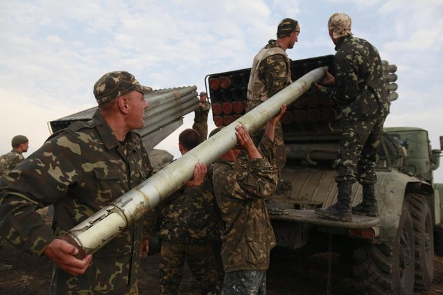 Ukrainian soldiers load a Grad missile during fighting with pro-Russian separatists close to Luhansk, eastern Ukraine, Monday, August 18, 2014. Dozens of civilians were killed Monday when separatist rebels shelled a convoy of refugees trying to flee war-torn eastern Ukraine, a top Ukrainian official said. A top rebel chief said no such attack had occurred. (Photo by Petro Zadorozhnyy/AP Photo)