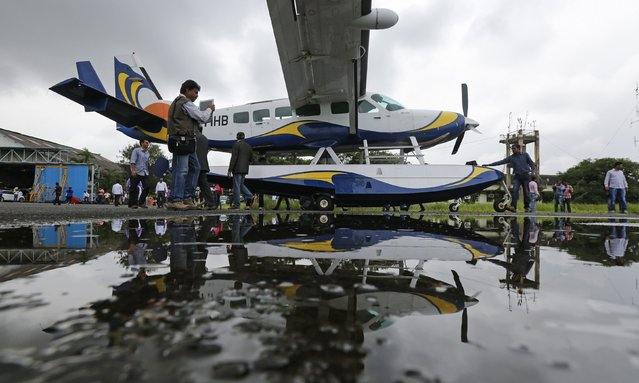 A man take a picture of a Cessna 208 Caravan 1 seaplane before it departs off from Juhu Aerodrome in Mumbai August 25, 2014. According to a media release, Mumbai's first leg of the commercial seaplane service connects the city to Pawna Dam, a water body near Lonavala, a popular tourist destination. (Photo by Shailesh Andrade/Reuters)