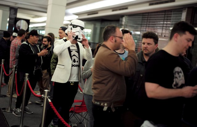 """A shopper wearing an Imperial Stormtrooper helmet waits with other Star Wars fans for the midnight opening of a Sydney department store selling new toys from the upcoming film """"Star Wars: The Force Awakens"""" on """"Force Friday"""" in Sydney, September 4, 2015. (Photo by Jason Reed/Reuters)"""