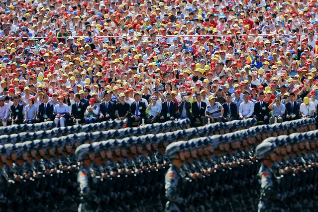 Guests watch and take pictures as China's People's Liberation Army soldiers march with their weapons at Tiananmen Square during the military parade marking the 70th anniversary of the end of World War Two, in Beijing September 3, 2015. (Photo by Damir Sagolj/Reuters)