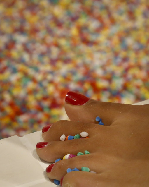 Sprinkles get caught between a visitor's toes from a large pool filled with 11,000-pounds of faux confetti-colored sprinkles, the biggest attraction of ice cream-themed works of art previewed at the Museum of Ice Cream, Thursday July 28, 2016, in New York. (Photo by Bebeto Matthews/AP Photo)