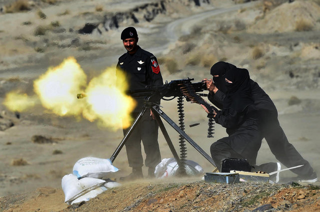 A Pakistani policewoman fires a heavy machine gun during a special elite police training course at a police training centre in Nowshera, a district in the Khyber Pakhtunkhwa Province on February 11, 2015. Dozens of male and female police took part in a commando training course, introduced by the local police as an additional skill for the police to be deployed to confront terrorism and extremism which is routinely on the rise in this South Asian nuclear-armed country. (Photo by A. Majeed/AFP Photo)