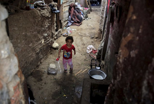 A boy stands outside his family house in the Eshash el-Sudan slum in the Dokki neighbourhood of Giza, south of Cairo, Egypt September 2, 2015. (Photo by Amr Abdallah Dalsh/Reuters)