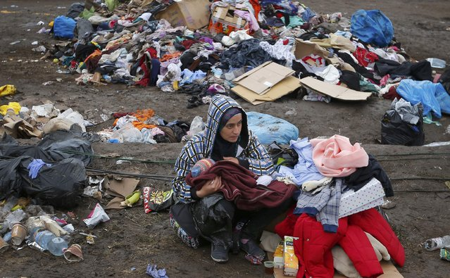 A mother breastfeeds her baby in front of piles of rubbish at a migrant collection point in Roszke, Hungary September 11, 2015. (Photo by Laszlo Balogh/Reuters)