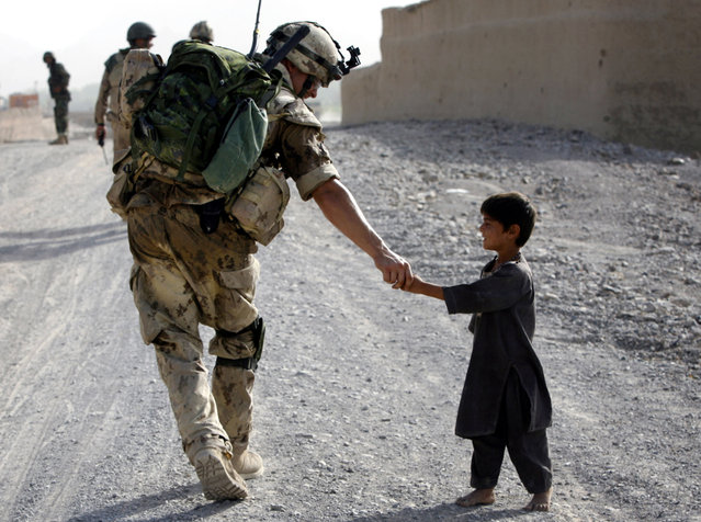 A Canadian soldier shakes hands with an Afghan boy during a joint patrol with Afghan National Army troops near Panjwaii village, Kandahar province, southern Afghanistan, July 13, 2007. (Photo by Finbarr O'Reilly/Reuters)