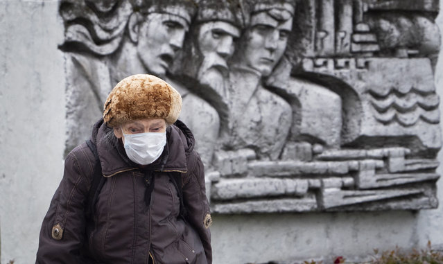 A woman wearing a face mask to protect against coronavirus walk past a Soviet era bas-relief in St. Petersburg, Russia, Thursday, May 21, 2020. (Photo by Dmitri Lovetsky/AP Photo)