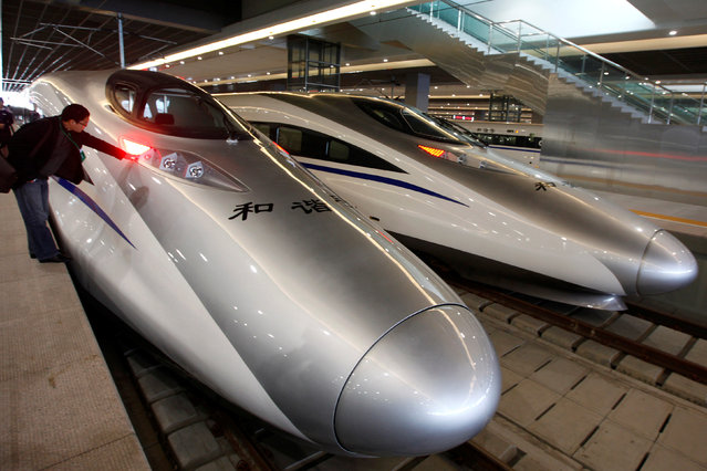 A man looks at the bullet trains serving the new high-speed railway linking Shanghai and Hangzhou in Shanghai October 26, 2010. (Photo by Aly Song/Reuters)