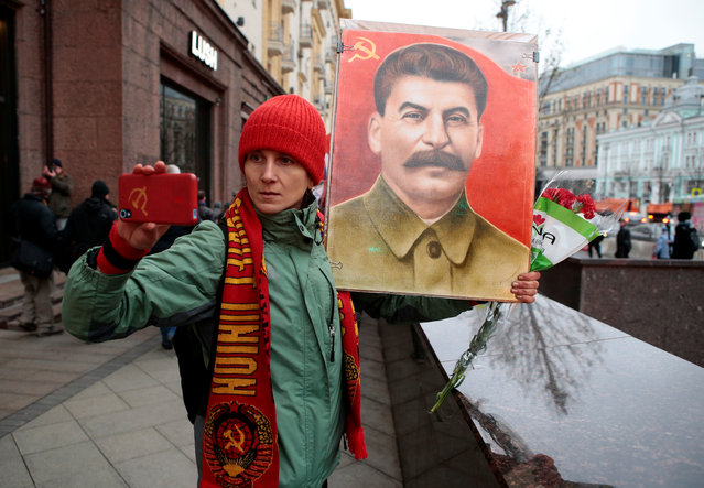 A demonstrator takes a selfie with a portrait of Soviet dictator Josef Stalin during a rally held by Russian Communist party to mark the Red October revolution's centenary in central Moscow, Russia on November 7, 2017. (Photo by Andrey Volkov/Reuters)