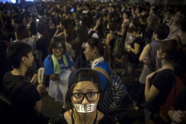 "A protester covers her mouth with tape that says ""democracy"" on the streets on September 30, 2014 in Hong Kong. (Photo by Paula Bronstein/Getty Images)"