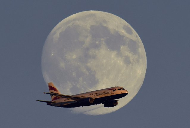 A British Airways passenger aircraft passes in front of the moon as it makes it's landing approach towards Heathrow Airport in west London in this photograph taken on July 18, 2016. (Photo by Toby Melville/Reuters)