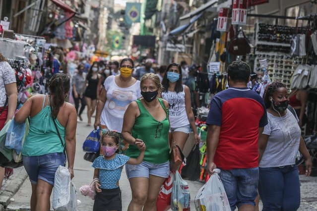 Shoppers wearing face masks walk at the Saara commercial center amidst the coronavirus (COVID-19) pandemic on June 27, 2020 in Rio de Janeiro, Brazil. Mayor Marcelo Crivella moved forward the reopening of street commerce in Rio de Janeiro. The establishments are authorized to operate between 11 AM and 5 PM. According to the mayor, the reopening was approved by the city council's scientific committee. (Photo by Andre Coelho/Getty Images)
