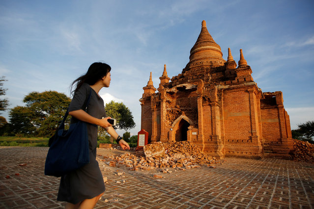 A woman walks past a damaged pagoda after an earthquake in Bagan, Myanmar August 25, 2016. Rescue workers surveyed the damage Thursday after a powerful earthquake shook Myanmar, killing at least four people and damaging 185 ancient Buddhist pagodas in the former capital of Bagan, a major tourist site. (Photo by Soe Zeya Tun/Reuters)