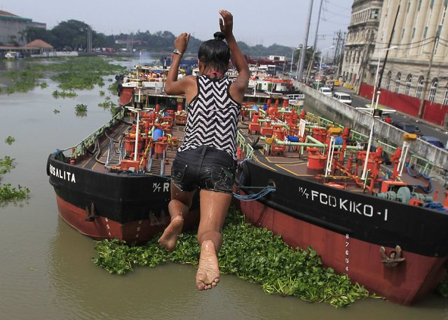 A girl dives in the polluted waters of the Pasig river as she goes for a swim to cool off in Manila October 11, 2014. (Photo by Romeo Ranoco/Reuters)