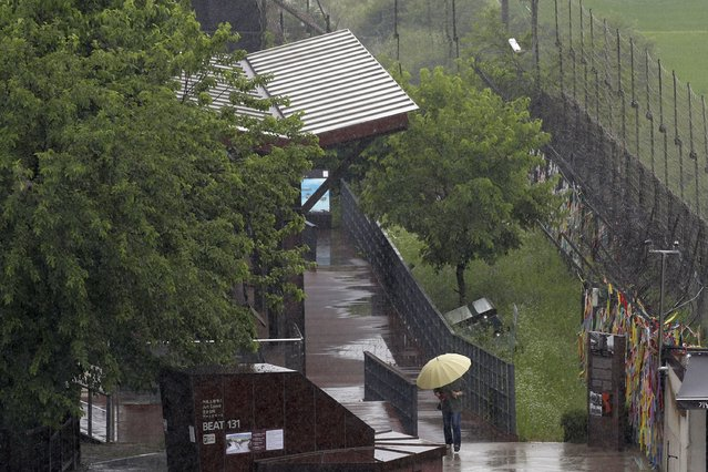 A woman holding an umbrella in rain, walks near the wire fences decorated with ribbons written with messages wishing for the reunification of the two Koreas at the Imjingak Pavilion in Paju, South Korea, Wednesday, June 24, 2020. North Korea said Wednesday leader Kim Jong Un suspended a planned military retaliation against South Korea, possibly slowing the pressure campaign it has waged against its rival amid stalled nuclear negotiations with the Trump administration. (Photo by Lee Jin-man/AP Photo)
