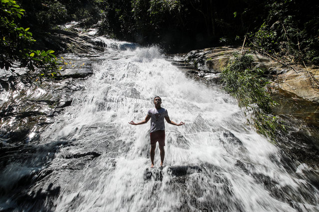 """A man reacts as his partner (not seen) takes his picture at the waterfall in Hulu Langat river, outside Kuala Lumpur, Malaysia, 01 July 2020. """"Recreational activities at swimming pools, rivers, lakes and in the sea will be allowed from 01 July"""", according to Senior Minister for Security Ismail Sabri Yaakob on 22 June. (Photo by Fazry Ismail/EPA/EFE)"""