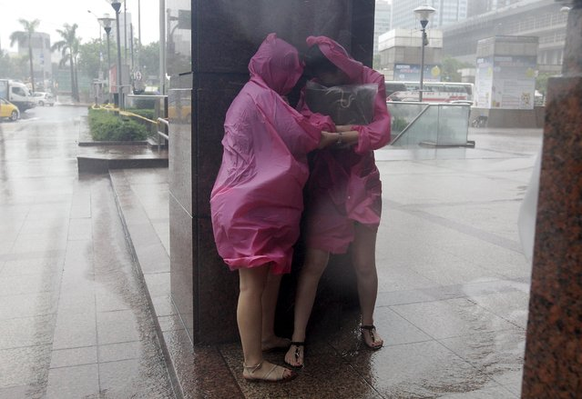 People try to take shelter against strong winds caused by Typhoon Dujuan by standing behind the column of a building in Taipei, Taiwan, September 28, 2015. (Photo by Pichi Chuang/Reuters)
