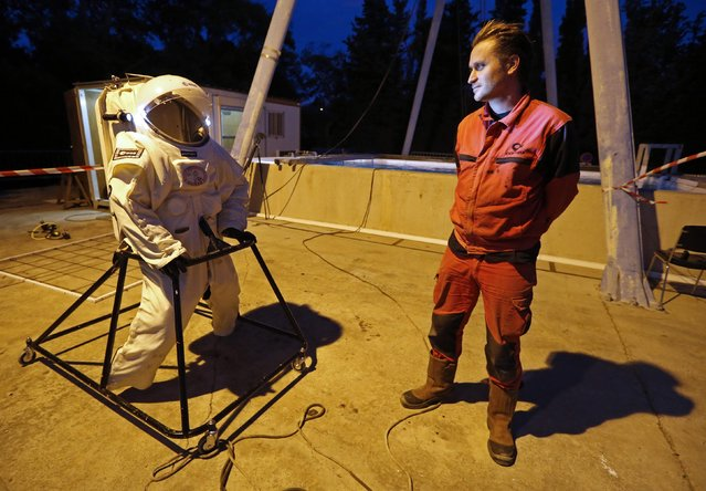 """Comex Space division manager Peter Weiss (R) looks at the Gandolfi space suit before a training session in Marseille October 22, 2014. The underwater test session develops European expertise in spacewalk simulations under partial gravity for exploring the Moon, asteroids and Mars.The training is organised by Comex, a French company specializing in engineering and deep sea diving operations, in collaboration with the European Space Agency (ESA) and with Apollo XI """"Under the sea"""". (Photo by Jean-Paul Pelissier/Reuters)"""