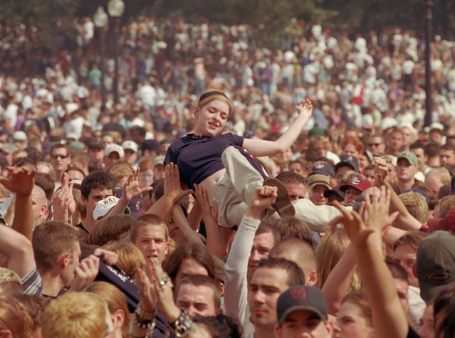 A young woman rides on the hands of people in the crowd as they dance and listen to music at the eighth annual Freedom Rally, sponsored by Mass Cann, a group committed to the legalization of marijuana, and the National Organization for the Reform of Marijuana Laws, on the Boston Common in Boston, Saturday, September 20, 1997. Over 50,000 people, mostly in their teens and early 20s attended the event where people openly smoked the drug. (Photo by Steven Senne/AP Photo)