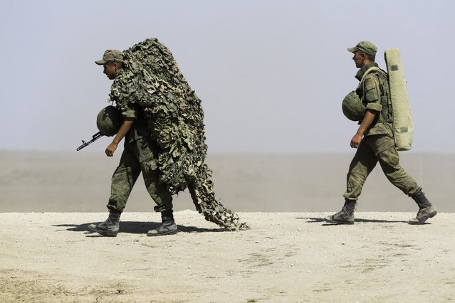 Russian soldiers carry their equipment during military drills at the Black Sea coast, Crimea, Friday, September 9, 2016. (Photo by Pavel Golovkin/AP Photo)