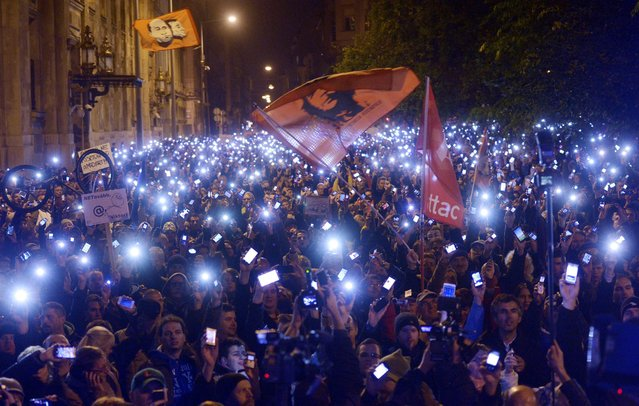 Thousands of demonstrators light up their mobile phones as they march through Elizabeth Bridge across River Danube as they protest against an internet tax planned to be introduced by the Hungarian government for the second time in two days in front of the Ministry of National Economy in Budapest, Hungary, Tuesday, October 28, 2014. (Photo by Laszlo Beliczay/AP Photo/MTI)