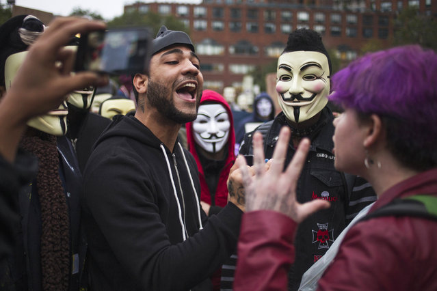 Activists, some wearing Guy Fawkes masks, debate with commuters during a demonstration in Union Square in Manhattan, New York November 5, 2014. (Photo by Adrees Latif/Reuters)