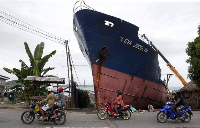 Residents ride their motorcycles past a ship which ran aground during last year's Typhoon Haiyan in Tacloban city in central Philippines November 4, 2014. The Philippines are preparing to commemorate victims of Typhoon Haiyan, ahead of the one-year anniversary of the disaster on November 8, according to a government official. (Photo by Erik De Castro/Reuters)