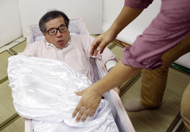 Yoshiya Yoshimura climbs out of a coffin after trying it out during an end-of-life seminar held by Japan's largest retailer Aeon Co in Tokyo October 24, 2014. (Photo by Toru Hanai/Reuters)