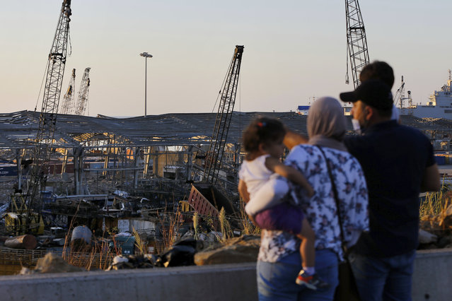 A family looks at the aftermath of the site of the Aug. 4 explosion that hit the seaport of Beirut, Lebanon, Sunday, August 16, 2020. (Photo by Bilal Hussein/AP Photo)