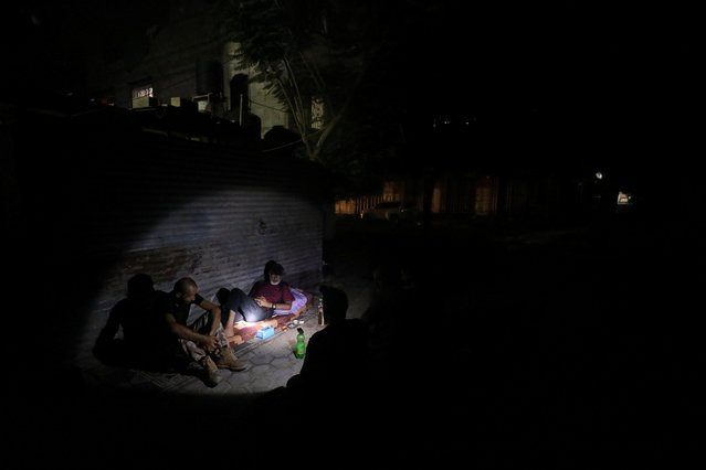 Palestinians, illuminated by a flashlight, rest outside their homes on a hot day during a power cut after Gaza's lone power plant shut down amid tension with Israel, in Jabalia refugee camp, in the northern Gaza Strip on August 23, 2020. Gaza's lone power plant shut down less than a week after Israel suspended fuel shipments to the Palestinian enclave over the launching of incendiary balloons that have caused brush fires in southern Israel. (Photo by Mohammed Salem/Reuters)