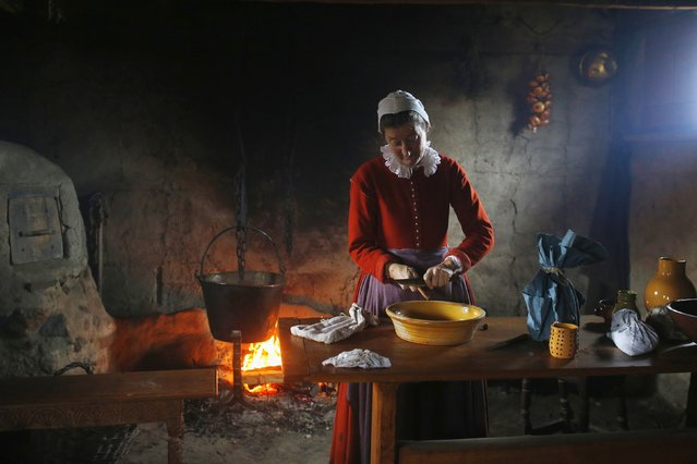A woman playing the role of Bridget Fuller scrapes cinnamon into a bowl to make pancakes in a home at Plimoth Plantation in Plymouth, Massachusetts November 24, 2014. Plimouth Plantation is a living museum portraying the life of the Native Americans and the English colonists in 1627, seven years after the colonists' arrival.  (Photo by Brian Snyder/Reuters)