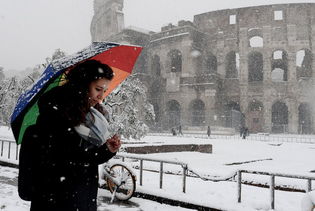 A woman shelters from the snow as she walks past The Colosseum on February 26, 2018 in Rome, Italy. The 'Beast from the East', an arctic storm set record low temperatures across much of Europe, with Rome seeing it's first snowfall in years. (Photo by Simona Granati - Corbis/Corbis via Getty Images)