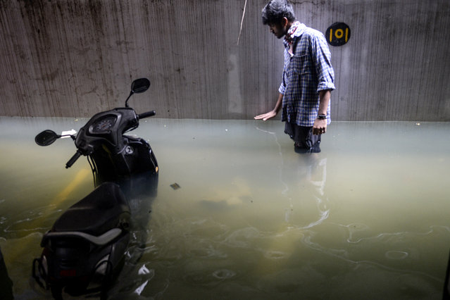 A resident shows the level of water in his cellar area at an apartment following heavy rains in Hyderabad on October 14, 2020. (Photo by Noah Seelam/AFP Photo)