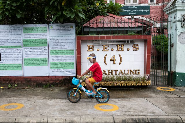 A kid wears a protective face shield, rides a bicycle in front of a closed high school in Yangon, Myanmar on August 28, 2020. Myanmar closed schools nationwide after reporting 70 new coronavirus infections on Wednesday. The country has reported more than 200 cases of the coronavirus since early last week after a month without any reports of domestic transmission. (Photo by Shwe Paw Mya Tin/NurPhoto via Getty Images)