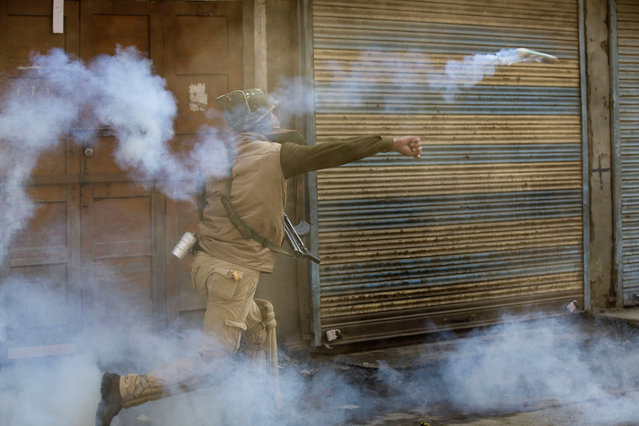 An Indian policeman throws back an exploded tear gas shell towards Kashmiri Muslim protesters during a protest in Srinagar, Indian controlled Kashmir, Friday, October 30, 2015. Police fired teargas and rubber bullets to disperse Kashmiris who gathered after Friday afternoon prayers to protest against the killing of Abu Qasim, a Pakistani national and operations chief of the Lashkar-e-Taiba militant group. (Photo by Dar Yasin/AP Photo)